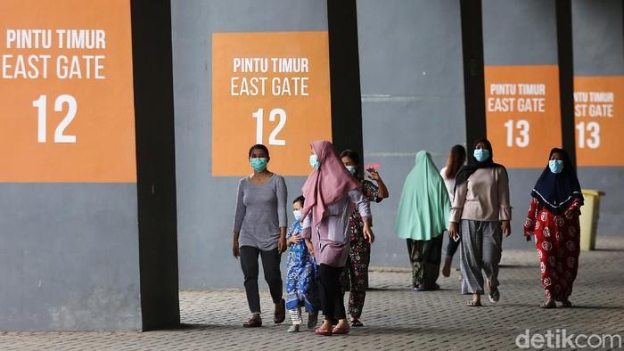 Petugas medis menggunakan Alat Pelindung Diri (APD) memeriksa kondisi pasien COVID-19 yang berstatus OTG (Orang Tanpa Gejala) saat kegiatan berjemur dan olahraga di Stadion Patriot Candrabhaga, Bekasi, Jawa Barat, Senin  (21/12/2020). Kegiatan pemeriksaan kesehatan, berjemur dan berolahraga tersebut rutin dilakukan setiap pagi hari untuk meningkatkan daya tahan tubuh pasien yang menjalani isolasi.