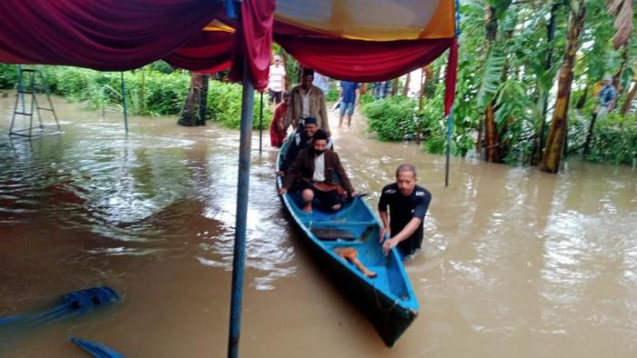 Penghulu di Maros terbos banjir pakai perahu demi nikahkan warga (Bakrie/detikcom).