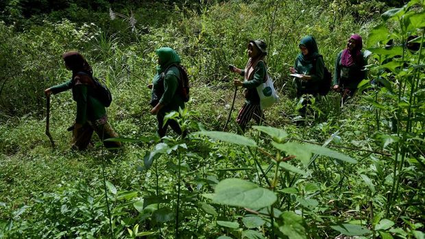 This picture taken on November 25, 2020 shows a group of women forest rangers patrolling in the forest of Bener Meriah, Aceh province. (Photo by CHAIDEER MAHYUDDIN / AFP) / TO GO WITH: Indonesia environment forests gender social, FEATURE by Alfath Asmunda