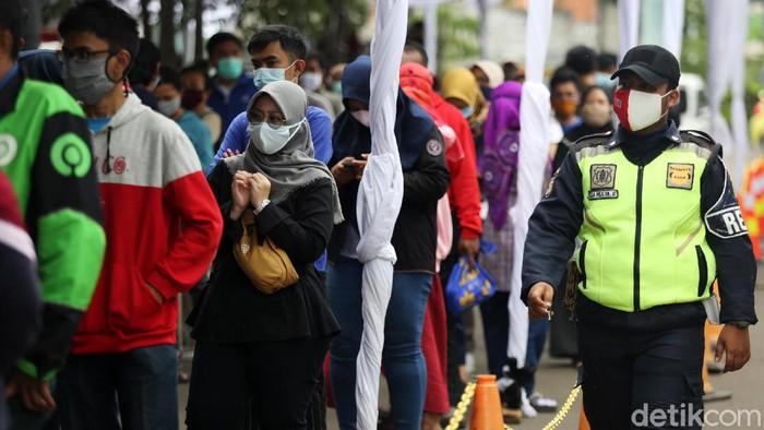 Para penumpang yang akan berangkat besok mendatangi Stasiun Pasar Senen untuk menjalani rapid test antigen. Antrean pun mengular panjang.