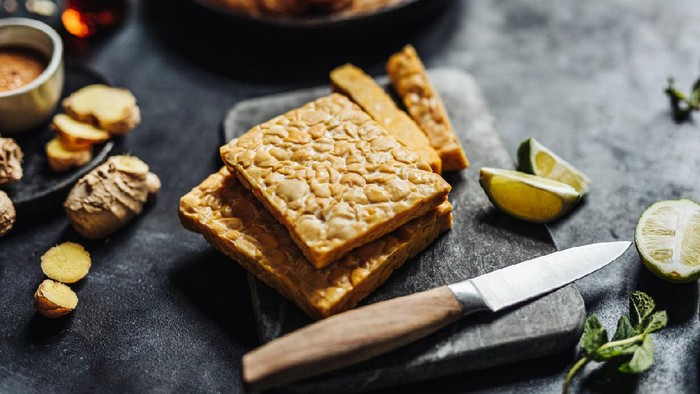 Close-up of tempeh on cutting board with kitchen knife with other ingredients on table. Preparing a vegan dish in kitchen.