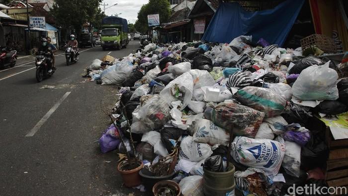 Warga melintas di depan tumpukan sampah yang membludak menutupi separuh jalan di depan gerbang Kampung Bausasran, Kota Yogyakarta, Senin (21/12/2020).