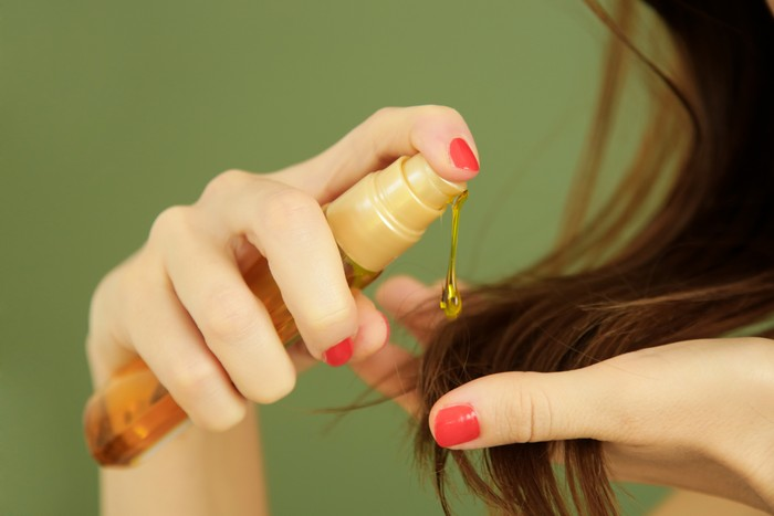 Woman applying oil on hair ends, split hair tips, dry hair or sun protection concept