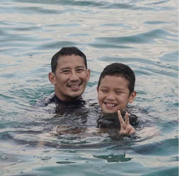 Bersama putranya Sulaiman saat berenang di Pantai Pemuteran, Bali. (sandiuno/Instagram)