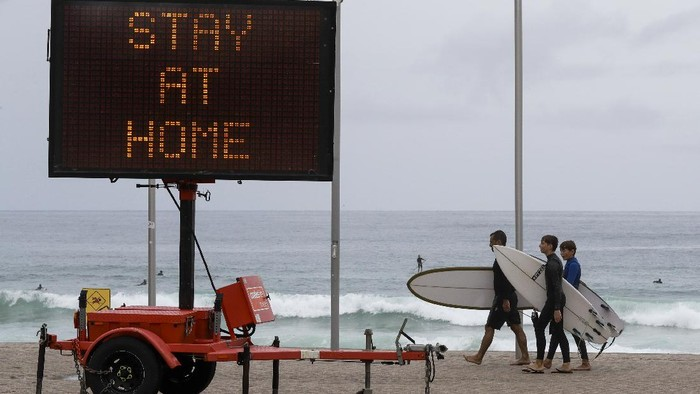 Surfers carry their boards along the beach front at Manly on the northern beaches in Sydney, Australia, Monday, Dec. 21, 2020. Sydneys northern beaches are in a lockdown similar to the one imposed during the start of the COVID-19 pandemic in March as a cluster of cases in the area increased to more than 80. (AP Photo/Mark Baker)