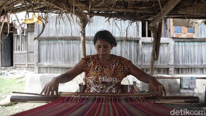 Magdalena Riwu, penenun asli Kabupaten Malaka tengah menenun di area pekarangan rumahnya, Malaka, Timor Tengah Selatan, NTT.