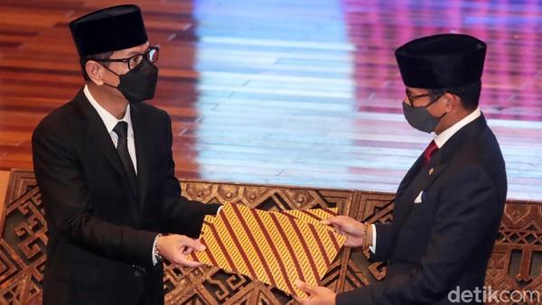 Wishnutama dan Sandiaga bertukar berita acara serah terima jabatan yang telah ditandatangani.