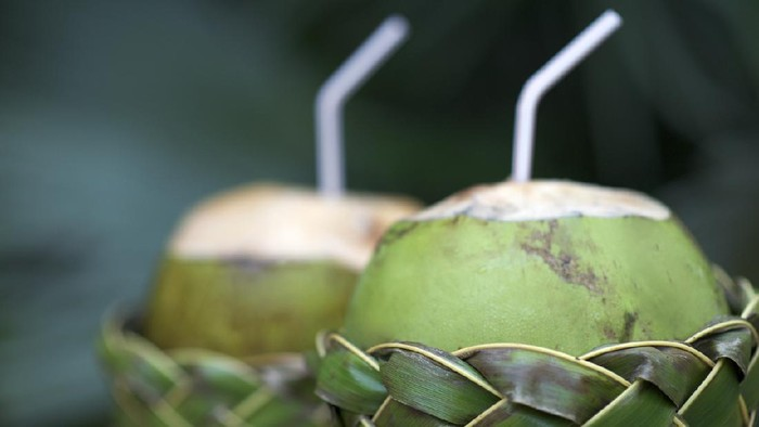 Fresh Brazilian coco gelado drinking coconuts in woven palm baskets rest on weathered wooden table against green jungle background