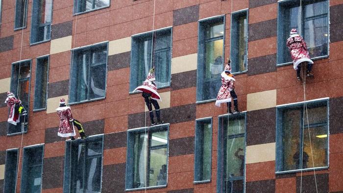 Meski di tengah pandemi COVID-19, Santa Klaus ini tidak kehabisan akal untuk menghibur anak di rumah sakit. Mereka memanjat tembok demi anak-anak.