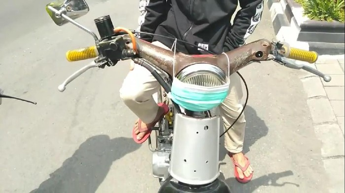 Pemotor nyeleneh pakai masker di lampu motor