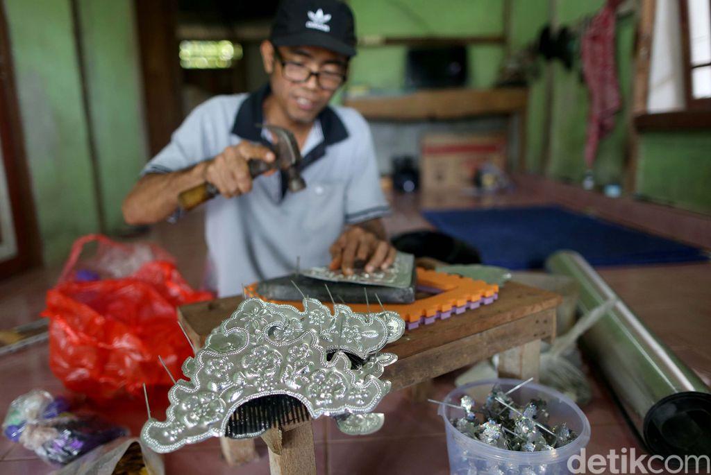 Nasabah KUR Mikro BRI, Ade Sanjaya yang juga penyintas Disabilitas menyelesaikan kerajinan Sugu Tinggi Iban di kediamannya, Badau, Kalimantan Barat. Dari hasil kerajinannya itu, ia bisa meraih Omzet Rp 5 juta per/bulan. Sebagian besar Sugu Tinggi itu di ekspor ke negara tetangga Malaysia dan Brunei Darussalam dan juga ke dalam negeri atau warga sekitar.