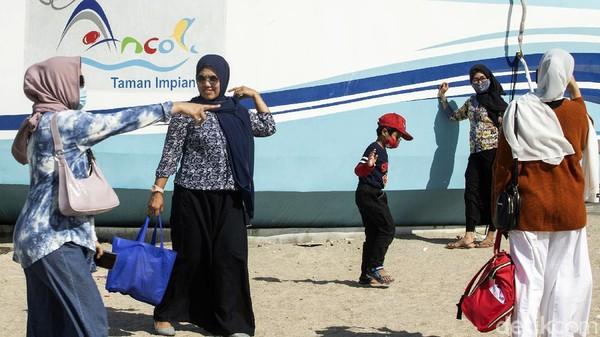 Pengunjung berfoto-foto di kawasan Pantai Ancol.
