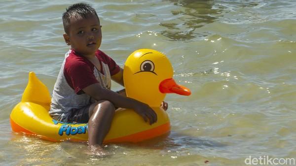Seorang anak asyik berenang.