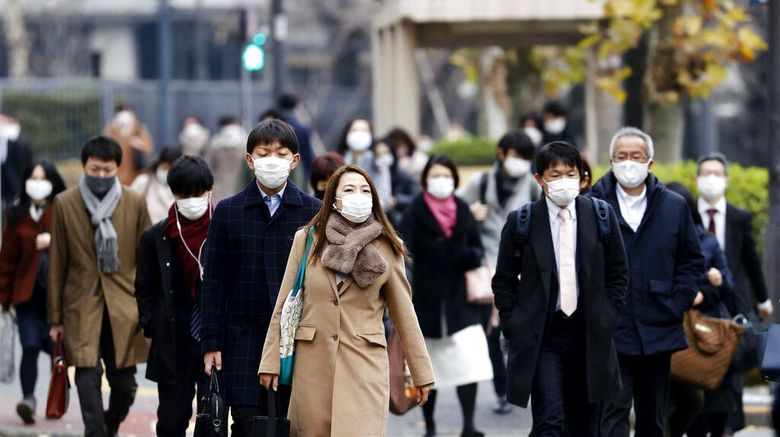 People wearing face masks to help curb the spread of the coronavirus walk in a business district in Tokyo Monday, Dec. 28, 2020. Japanese Prime Minister Yoshihide Suga says he plans to submit legislation that will make coronavirus measures legally binding for businesses, punish violators and include economic compensation as his government struggles to slow the ongoing upsurge.(Kyodo News via AP)