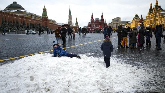 A boy plays on a pile of snow in Red Square decorated for Christmas and New Year celebrations, without the Christmas Market due to the virus-related restrictions, with the Kremlin Wall, the Historical Museum and GUM in the background in Moscow, Russia, Saturday, Dec. 26, 2020. The temperature in Moscow is about 0 degree Celsius (32 degree Fahrenheit). (AP Photo/Alexander Zemlianichenko)