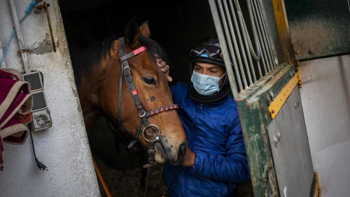 Turf horse race aficionados follow a race at the Hipodromo de la Zarzuela outskirts of Madrid, Spain, Sunday, Dec. 6, 2020.  The pandemic may have altered many habits but horse racing at the Zarzuela has changed little. (AP Photo/Bernat Armangue)