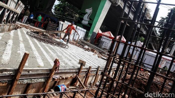 Sejumlah pekerja merampungkan pengerjaan bangunan dalam proyek penataan plaza Stasiun Tebet di kolong jembatan layang Tebet, Jakarta Selatan, Selasa (29/12/2020). Stasiun Tebet akan ditata layaknya Stasiun Tanah Abang untuk mengoptimalkan integrasi antarmoda bagi penumpang yang mengakses transportasi kereta api.