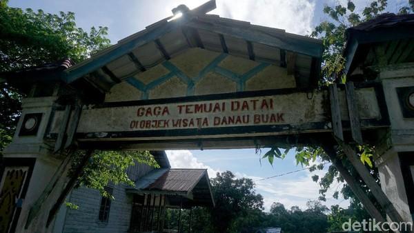 Sebuah gapura bertuliskan nama objek wisata Danau Buak ini pun sudah pudar seperti tak terawat.