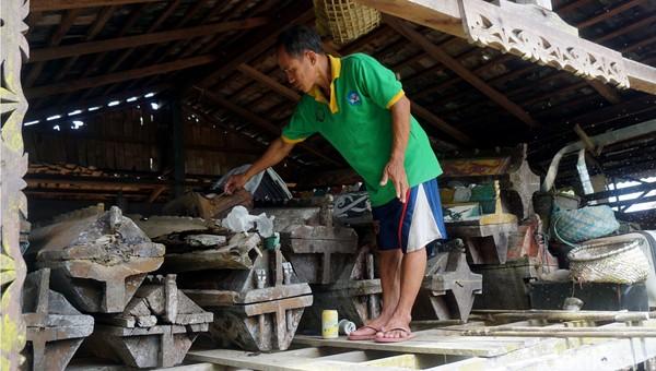 Juru Rawat Rumah Mayat Kulambu, Dominikus Giling menunjukkan salah satu peti mati. Menurutnya, pemindahan jenazah diambil dengan perahu hiasan, prosesnya juga dilakukan dengan tembakan dengan diirinig musik tradisi.