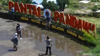 Beberapa wisatawan terlihat berpose di landmark Pantai Pandawa.