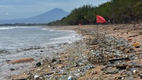 Wisatawan berjalan melewati sampah kiriman yang memenuhi pesisir Pantai Kuta, Badung, Bali, Kamis (31/12/2020).