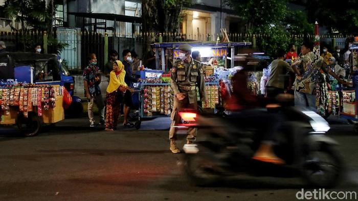 Sejumlah personel Satpol PP melaukan penertiban puluhan PKL di kawasan Kota Tua, Jakarta. Hal itu dilakukan untuk mencegah kerumunan di malam pergantian tahun.
