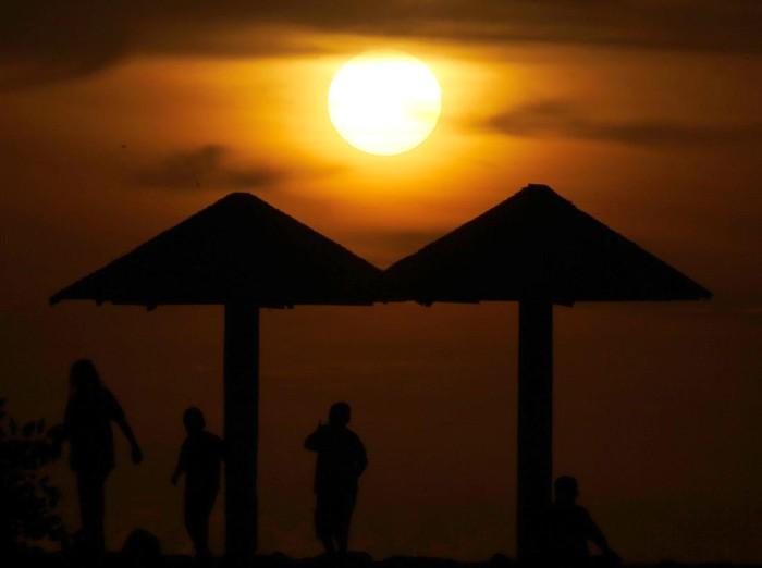 Warga menikmati panorama alam matahari terbenam (sunset) akhir tahun 2020 di pantai Babah Kuala Lampuuk, Aceh Besar, Aceh, Kamis (31/12/2020). Menikmati sunset di provinsi paling ujung barat pulau Sumatera menjadi wisata alternatif bagi sebagian warga setelah adanya larangan perayaan pergantian tahun masehi di provinsi Aceh. ANTARA FOTO/Irwansyah Putra/rwa.