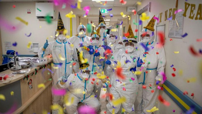 ROME, ITALY - DECEMBER 31: Healthcare workers in personal protective equipment (PPE) celebrate the new year in the Intensive Care Unit (ICU) on New Years Eve in the COVID-19 department of the San Filippo Neri Hospital amid the coronavirus pandemic, on December 31, 2020, in Rome, Italy. Hospitals in Italy are under pressure as they battle to treat those who have contracted COVID-19 in final days of 2020. The Italian government continues to enforce national lockdown measures to control the spread of COVID-19. There have been over 2,070,000 reported coronavirus (COVID-19) cases in Italy and more than 73,029 related deaths since the beginning of the pandemic. (Photo by Antonio Masiello/Getty Images)