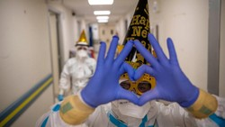 Di tengah perjuangan melawan COVID-19, para tenaga kesehatan di Italia merayakan pergantian tahun dengan para pasiennya. Atribut tahun baru pun mereka kenakan.