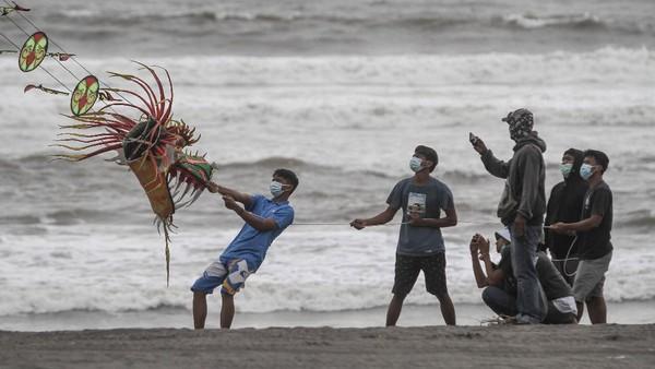 Guna mengantisipasi penyebaran virus Corona, para wisatawan yang datang berkunjung ke Pantai Parangkusumo tampak mengenakan masker.