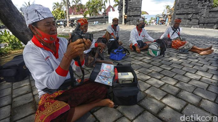 Pandemi Corona yang merebak membuat sejumlah fotografer di Tanah Lot, Bali harus bekerja lebih keras.