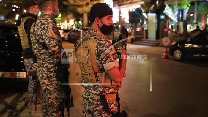 Lebanese security forces wearing protective masks to prevent the spread of coronavirus, as they stand guard at a street full of restaurants where revelers celebrating the New Year Eve, in Beirut, Lebanon, early Friday, Jan. 1, 2021. Lebanon ended the year with more than 3,500 newly registered infections of coronavirus and 12 new deaths as its health minister rang appealed to Lebanese to take precautions while celebrating to avoid what he called wasting sacrifices made in combatting the virus. (AP Photo/Hussein Malla)