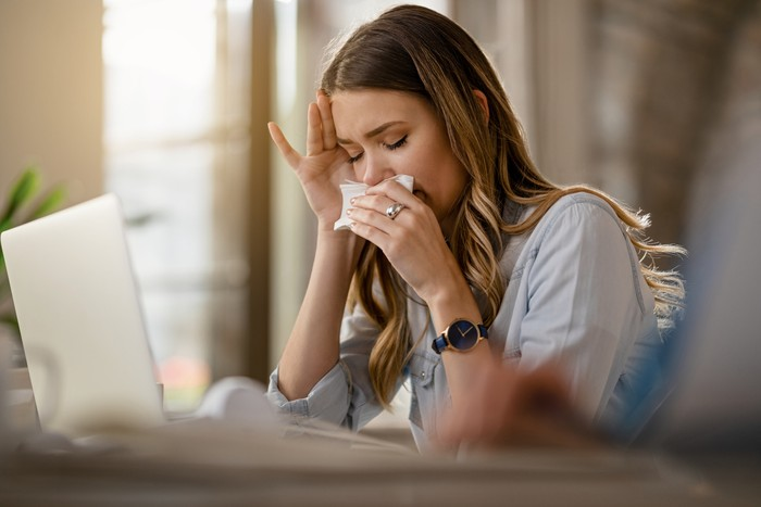 Young businesswoman with clpd and flu virus blowing nose while working in the office.