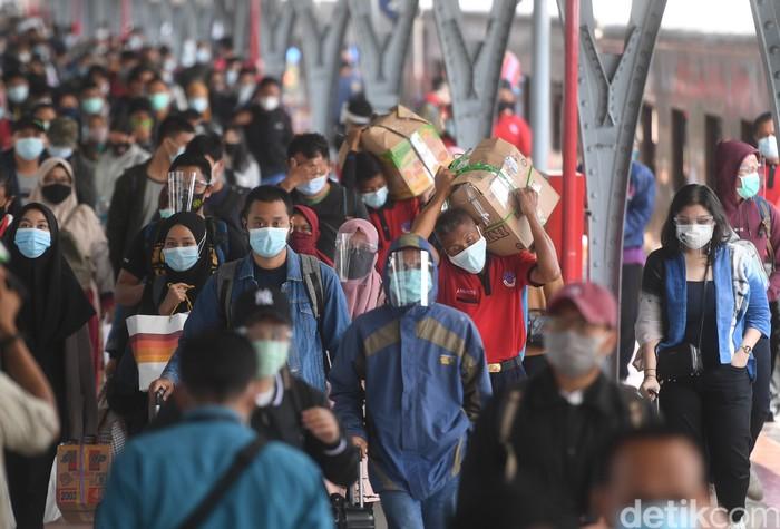 Puncak arus balik libur tahun baru diprediksi terjadi hari ini, Minggu (3/1/2021). Stasiun Pasar Senen pun disibukkan dengan kedatangan ribuan penumpang.