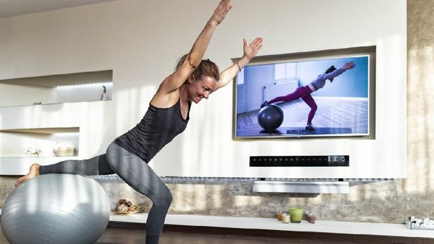 Happy athletic woman exercising during live streaming sports training over television in the living room.