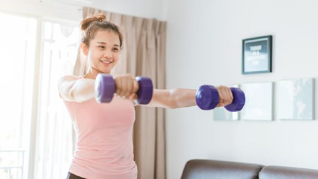 A woman wearing sports clothes raised a dumbbell exercise in the living room. She is training at home. woman in sportswear with Purple dumbbells in her hands.