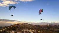 Para penerbang paraglider juga memanfaatkan musim dingin untuk terbang di atas Mam Tor, bukit setinggi 517m dekat Castleton di Inggris tengah. Danny Lawson/PA via AP