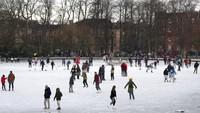 Orang-orang berjalan dan berseluncur es di kolam beku di Queens Park di Glasgow. Andrew Milligan/PA via AP
