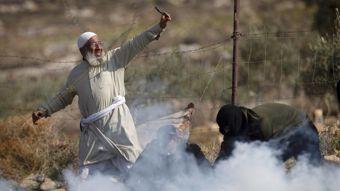Palestinian protesters use slingshots to hurl stones towards Israeli troops during a protest against Israeli settlements, in the West Bank village of Deir Jarir, north of Ramallah, Friday, Jan. 1, 2021. (AP Photo/Majdi Mohammed)