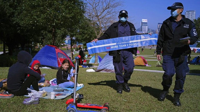 A police officer displays a banner showing social distancing to prevent the spread of coronavirus at a park in Hong Kong Saturday, Jan. 2, 2021. (AP Photo/Vincent Yu)