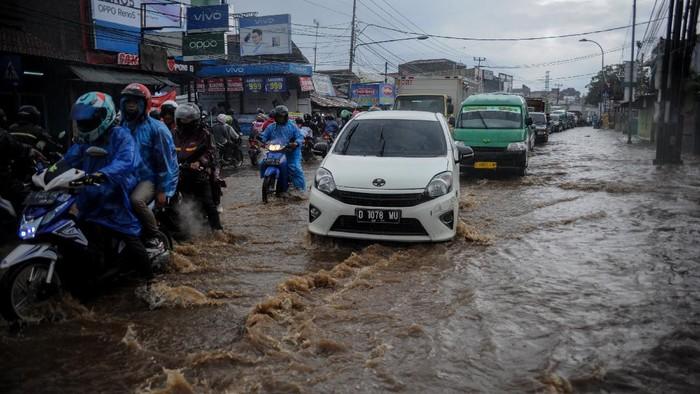 Kendaraan menerjang air yang menggenangi Jalan Raya Cinunuk, Kabupaten Bandung, Jawa Barat, Senin (4/1/2021). Genangan air setinggi 10 hingga 50 sentimeter menggenangi Jalan Nasional menuju Sumedang, Tasik dan Garut akibat drainase yang buruk sehingga tidak dapat menampung debit air secara maksimal saat hujan lebat mengguyur kawasan Bandung Raya. ANTARA FOTO/Raisan Al Farisi/foc.