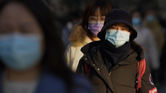 People wearing face masks to help curb the spread of the coronavirus walk through commercial office buildings in Beijing, Monday, Jan. 4, 2021. Wary of another wave of infections, China is urging tens of millions of migrant workers to stay put during next month's Lunar New Year holiday, usually the world's largest annual human migration. (AP Photo/Andy Wong)