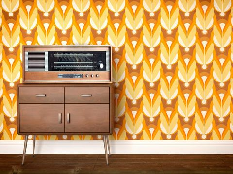Vintage old radio from eastern Europe (labels indicate cities of the eastern block, including former GDR, East Germany) laying on a piece of furniture and a background showing a sixties, seventies design wallpaper pattern. Copy space on the side for customization.