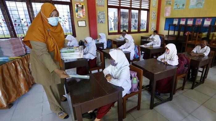 Pelajar membenahi masker adiknya pada hari pertama sekolah tatap muka di SD Negeri 42, Banda Aceh, Aceh, Senin (4/1/2021). Mayoritas lembaga pendidikan tingkat SD, SMP, dan SMA di provinsi Aceh mulai melaksanakan pembelajaran tatap muka dengan sistim bergiliran dan menerapkan protokol kesehatan secara ketat untuk mencegah penularan COVID-19. ANTARA FOTO/Irwansyah Putra/hp.