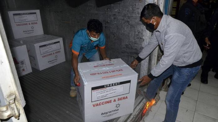 Pekerja memindahkan vaksin COVID-19 Sinovac dari dalam truk di UPTD Instalasi Farmasi dan Kalibrasi Dinas Kesehatan Provinsi Lampung, Lampung, Senin (4/12/2020) malam. Sebanyak 40.520 ribu dosis vaksin COVID-19 Sinovac tiba di Lampung dan disimpan di raung khusus di UPTD Instalasi Farmasi dan Kalibrasi Dinas Kesehatan Provinsi Lampung . ANTARA FOTO/Ardiansyah/hp.