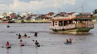 Sejumlah anak bermain perahu kano di Sungai Kapuas, Pontianak, Kalimantan Barat, Minggu (3/1/2021).