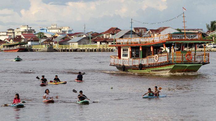 Puluhan wisatawan domestik menaiki kapal wisata di Sungai Kapuas, Pontianak, Kalimantan Barat, Minggu (3/1/2021). Wisata Sungai Kapuas tersebut menjadi salah satu destinasi bagi warga setempat untuk menghabiskan libur tahun baru. ANTARA FOTO/Jessica Helena Wuysang/rwa.