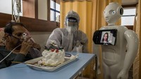 NEW DELHI, INDIA - DECEMBER 05: A Covid-19 patient connects with a family member with the assistance a robot as he receives a cake on his birthday on December 5, 2020 in New Delhi, India. The