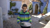 Seorang anak berkeliling salah satu area di Kota Chefchaouen, Maroko, untuk menjajakan kue buatan sendiri.