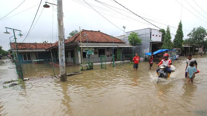 Warga melintasi banjir di Desa Widasari, Indramayu, Jawa Barat, Selasa (5/1/2021). Ratusan rumah di desa tersebut terendam banjir setingggi 50 cm hingga satu meter akibat luapan sungai Cibuaya. ANTARA FOTO/Dedhez Anggara/rwa.
